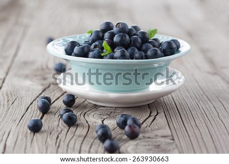 Juicy fresh blueberries in a blue bowl on old wooden background, selective focus - stock photo