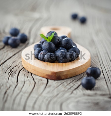 Juicy fresh blueberries on old wooden background, selective focus - stock photo