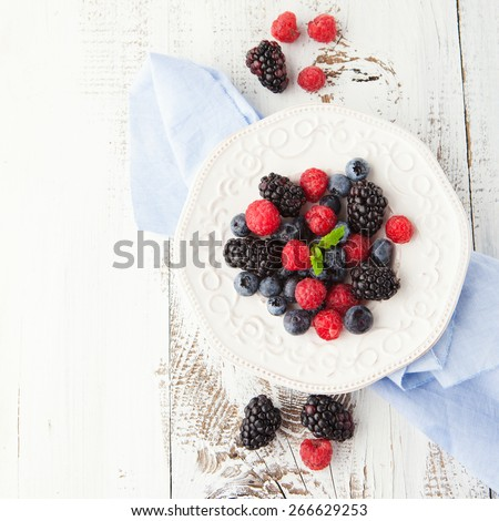 Juicy fresh blueberries, raspberries and blackberries in a plate on white wooden background, top view - stock photo