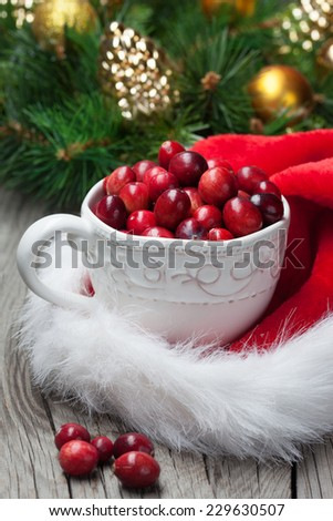 Juicy fresh cranberries in a cup on old wooden background, christmas time. - stock photo