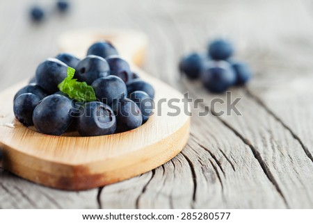 Juicy fresh ripe blueberries on rustic wooden background, selective focus - stock photo