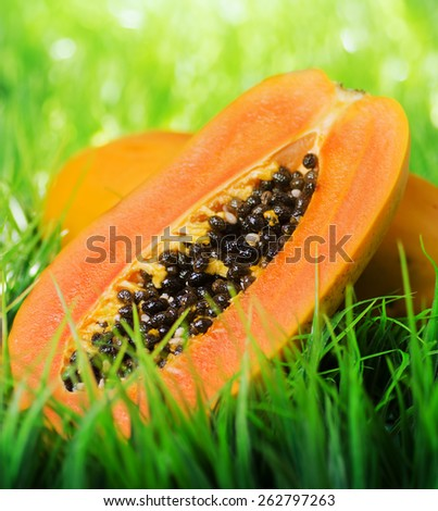 Juicy fresh yellow papaya on green grass. Healthy eco food rich in minerals and vitamins. Product of organic farming. - stock photo
