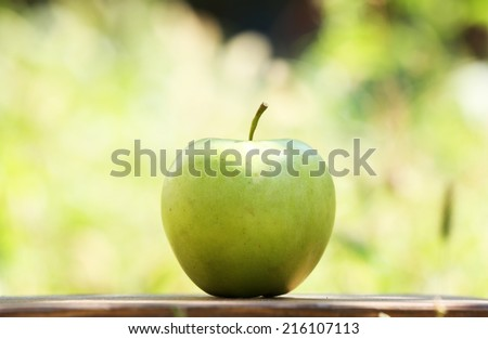 Juicy green apple on table, outdoors - stock photo