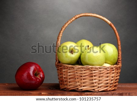 juicy green apples in basket and red apple on wooden table on gray background - stock photo