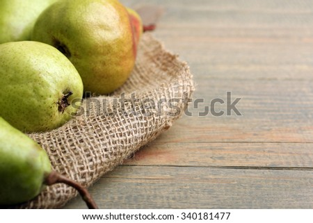 juicy green pears on fabric on brown wooden  background - stock photo