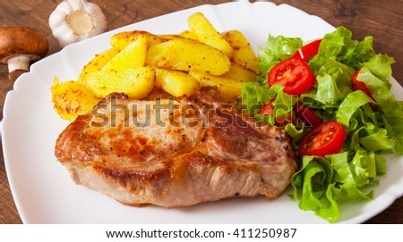Juicy grilled meat fillet steak with fried potato and vegetables salad in a plate on wooden table - stock photo