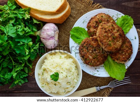 Juicy homecutlets (beef, pork, chicken) and mashed potatoes on a wooden background. The top view. - stock photo