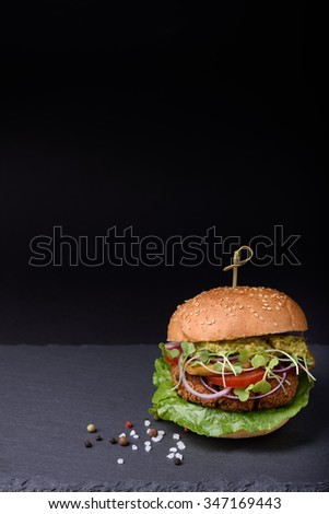 Juicy homemade hamburger with grilled beef cutlet, pepper, salad, tomato, mushrooms, onion served with pepper and sea salt on black stone board, space for text. - stock photo