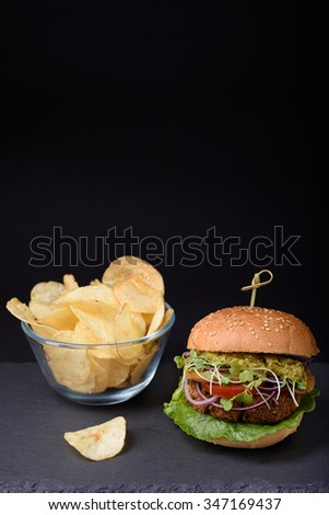 Juicy homemade hamburger with potato chips on slate board over black background. Copy space. - stock photo