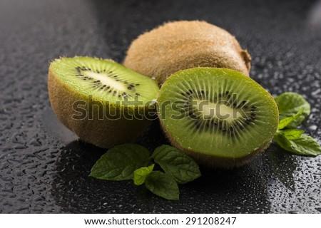 Juicy kiwi fruit and freas mint leaves - stock photo