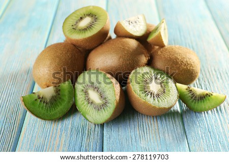 Juicy kiwi fruit on wooden background - stock photo