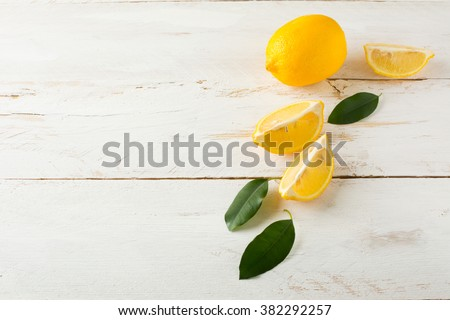 Juicy lemons with leaves on a white wooden background. Lemon slices. Fresh Lemon.  Fresh citrus fruit background.  - stock photo