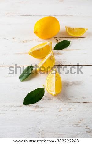 Juicy lemons with leaves on a white wooden background, vertical. Lemon slices. Lemon. Lemons. Citrus. Fruit. Fruits. Fresh Lemon. Juicy Lemons. Fresh Citrus. Fresh Fruit. Juicy Fruits. - stock photo