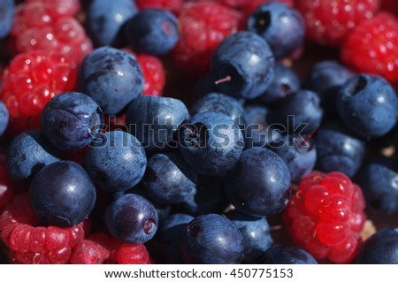 Juicy mature berries of bilberry and raspberry close up. Berry background - stock photo