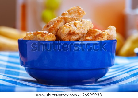 Juicy meat nuggets in blue bowl on checkered tablecloth. - stock photo
