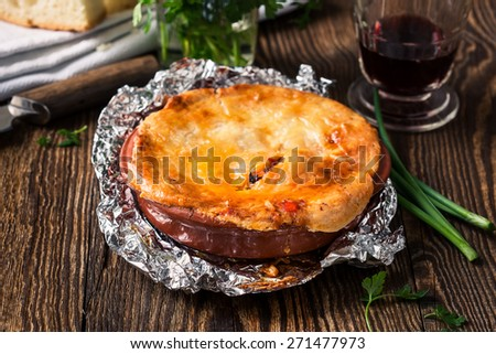 Juicy meat pot pie in a ceramic oven pot, beef stew pie with puff pastry - stock photo