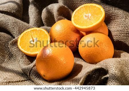 Juicy oranges on jute bag - stock photo