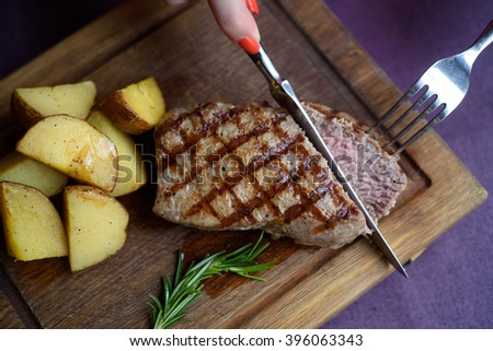 Juicy piece of beef steak with potato on a wooden board with knife and fork - stock photo