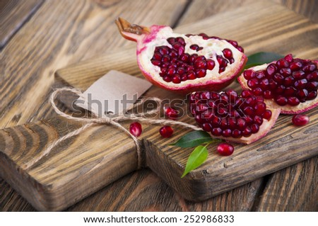 Juicy pomegranate and red grains on wooden background - stock photo