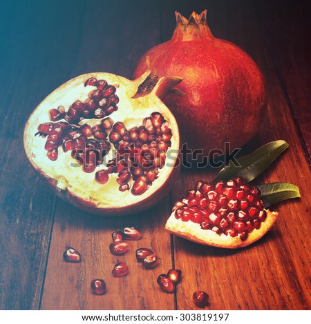 juicy pomegranate open on wood board.Filtered image: warm cross processed vintage effect. - stock photo