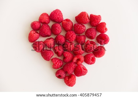 Juicy red heart made of organic fresh raspberries on white background. Healthy food for healthy life. Valentine's day - stock photo