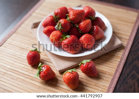 juicy, red strawberries in white plate, on a wooden texture - stock photo