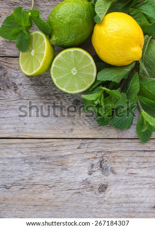 Juicy ripe citrus on an old wooden table - lime, lemon and mint. Ingredients for Mojito cocktail - stock photo