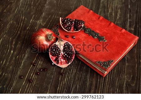 juicy ripe pomegranate with vintage red book on the wooden table. Rustic style - stock photo