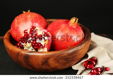 Juicy ripe pomegranates on wooden table, on dark background - stock photo