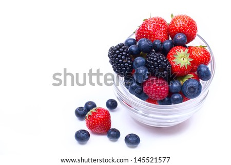 juicy, ripe strawberries, blueberries, raspberries and blackberries on a white background. in glass vases - stock photo