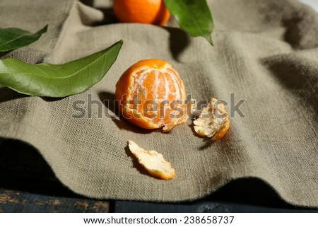 Juicy ripe tangerine with leaves on tablecloth - stock photo