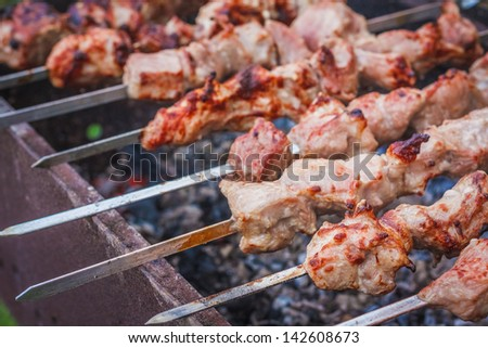 Juicy slices of meat with sauce prepare on fire (shish kebab). / Shish kebab in process of cooking on open fire outdoors - stock photo