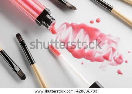 Juicy stains and drops of the lipstick on the white table. Objects in the foreground. Scattered brushes and applicators for applying make-up. - stock photo