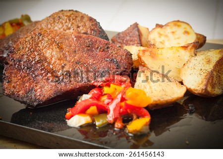 Juicy steaks served with roasted potatoes and peppers on black granite board, vignetted - stock photo