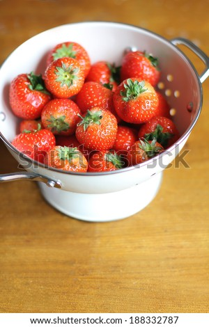 Juicy strawberry in a white colander - stock photo