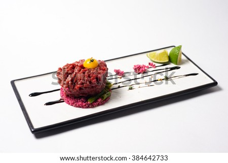 juicy Tartar of beef served with lime on white dish - stock photo