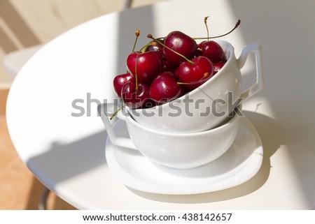 Juicy tasty red sweet cherries in mug on white table. Selective focus - stock photo