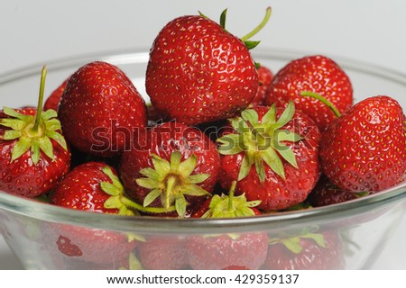 Juicy, tasty strawberry on the glass plate. Strawberries in a glass plate on white background. Close-up fresh strawberries lay on glass plate. - stock photo