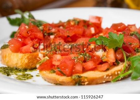 Juicy tomatoes on fresh bread, pesto as topping - stock photo