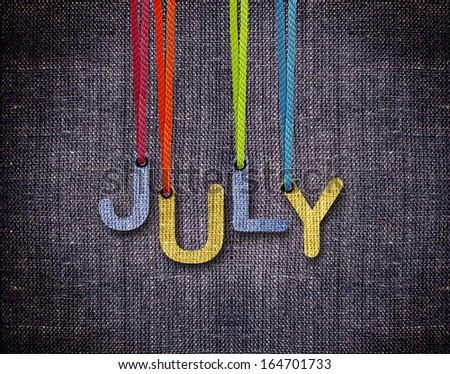 July letters hanging strings with blue sackcloth background. - stock photo