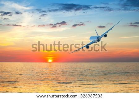 Jumbo jet airplane flying above tropical sea at beautiful sunset. - stock photo