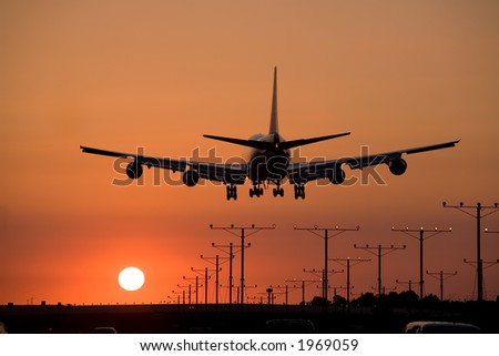 Jumbo jet coming in for a sunset landing - stock photo
