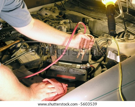 Jump starting a car late at night (typical lighting for night emergency) - stock photo