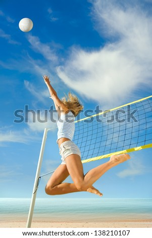 Jump up of sports young woman playing volleyball on sea beach - stock photo