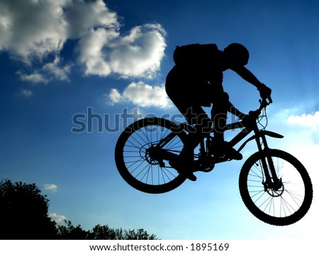 jump with a mountain bike - silhouette - stock photo