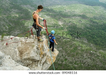 Jump with a rope into the canyon. - stock photo