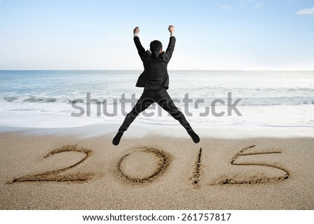 Jumping businessman cheering for new year 2015 on sand beach background - stock photo
