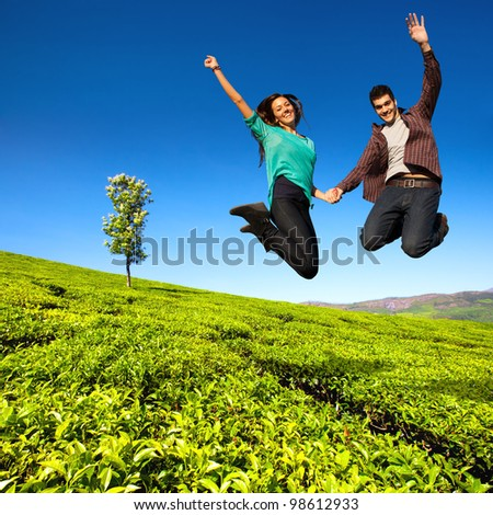 Jumping couple with hands raised in sunny green field. - stock photo