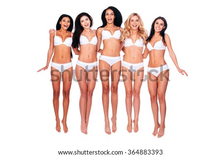 Jumping cuties. Full length of five happy young women in lingerie bonding to each other and jumping while against white background - stock photo