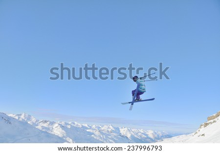 jumping freestyle skier at mountain with fresh snow fresh sunny winter day - stock photo